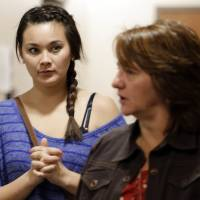 Photo - Chantel Blunk, left, is escorted by a victims assistant as she arrives for the third day of a preliminary hearing for Aurora theater shooting suspect James Holmes at the courthouse in Centennial, Colo., on Wednesday, Jan. 9,  2013. Chantel's husband Jon was killed in the shooting. (AP Photo/Ed Andrieski)