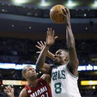 Photo - Boston Celtics' Jeff Green (8) shoots over Miami Heat's Shane Battier (31) in the first quarter of an NBA basketball game in Boston, Monday, March 18, 2013. (AP Photo/Michael Dwyer)