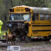 Photo - FILE - In a Wednesday, March 7, 2012 file photo, a Montgomery Count sheriff's deputy walks away from an old school bus where two children were found living on their own, in Spendora, Texas. Child Protective Services officials are expected to recommend a judge dismiss the welfare agency's case against Mark and Sherrie Shorten in court Tuesday, Jan. 22, 2013, allowing the couple to regain full custody of their 12-year-old daughter and 6-year-old son. The children were found by a postal worker living in an abandoned school bus while Shorten and her husband were in prison for embezzling money from victims of 2008's Hurricane Ike. ( AP Photo/Houston Chronicle, Brett Coomer, File)