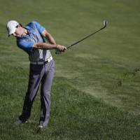 Photo - Rory McIlroy, of Northern Ireland, hits from the rough on the 14th hole during the second round of the Memorial golf tournament Friday, May 30, 2014, in Dublin, Ohio. (AP Photo/Darron Cummings)