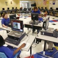 Photo - STUDENTS: Kids use computers in the newly constructed computer room at Telstar Elementary School in Oklahoma City, Okla., Thursday, November 10, 2006. The school is one of the recipients of