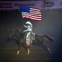 Photo -  The American flag is presented the National Circuit Finals Rodeo at the State Fair Arena in Oklahoma City, Friday, April 5, 2013. Photo by Sarah Phipps, The Oklahoman