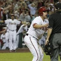 Photo - Arizona Diamondbacks' Miguel Montero, left, argues with umpire Tom Hallion, right, after Hallion initially called Montero out at home plate until he realized San Francisco Giants catcher Buster Posey dropped the ball during the fourth inning of an opening day baseball game, Monday, March 31, 2014, in Phoenix. (AP Photo/Ross D. Franklin)