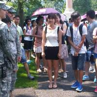 Photo -   In this photo of Aug. 3, 2012, a tourist poses with cadets for a photo as others wait their turn during a tour of the U.S. Military Academy at West Point, N.Y. Suburbs in the New York metropolitan area are stepping up their efforts to attract tourist dollars, not by competing with New York City, but by marketing themselves as complementary destinations. (AP Photo/Jim Fitzgerald)