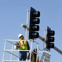 Photo - Workers with Traffic Systems Inc. install a new traffic signal at Robinson Street and Berry Road in Norman.