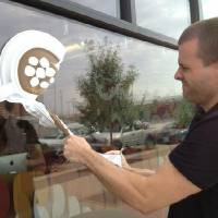 Photo - Oklahoma City Co-working Collaborative co-founder Derrick Parkhurst removes the group's storefront signage Monday after announcing it is closing its doors.  Meaghan Hadley
