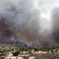 Photo - Wildfire climbs a canyon toward homes Wednesday, May 14, 2014, in Carlsbad, Calif. More wildfires broke out Wednesday in San Diego County — threatening homes in Carlsbad and forcing the evacuations of military housing and an elementary school at Camp Pendleton — as Southern California is in the grip of a heat wave. (AP Photo)