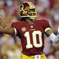 Photo - Washington Redskins quarterback Robert Griffin III passes the ball during the first half of an NFL football game against the New York Giants in Landover, Md., Monday, Dec. 3, 2012. (AP Photo/Patrick Semansky)