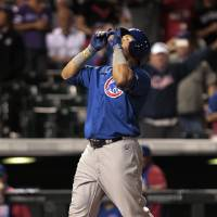 Photo - Chicago Cubs' Javier Baez looks skyward as he crosses home plate after his solo home run in the 12th inning of a baseball game against the Colorado Rockies in Denver on Tuesday, Aug. 5, 2014. (AP Photo/Joe Mahoney)