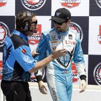 Photo - In this May 18, 2014 photo James Hinchcliffe, of Canada, talks with a crewman after his qualification run for the Indianapolis 500 IndyCar auto race at the Indianapolis Motor Speedway in Indianapolis. A week ago, there were questions that Hinchcliffe would be able to race in the Indianapolis 500 after suffering a concussion in the Grand Prix of Indianapolis. The 27-year old Canadian is not only cleared to drive, he's second on the grid for the most famous race in IndyCar (AP Photo/Tom Strattman)