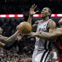 Photo - CORRECTS ORDER OF SPURS PLAYERS  - San Antonio Spurs' Kawhi Leonard, center, is fouled by Cleveland Cavaliers' Jarrett Jack, right, as Kyrie Irving, left, helps defend the play during the first half of an NBA basketball game Saturday, Nov. 23, 2013, in San Antonio. (AP Photo/Eric Gay)