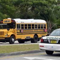 Photo -   Police investigate the scene of a shooting on a school bus in Homestead, Fla., near Miami, Tuesday, Nov. 20, 2012. Miami-Dade police say a 13-year-old girl has died after she was shot by another student on the school bus in Homestead. A male student is in custody and police spokesman Alvaro Zabaleta says investigators are talking to him. A gun was also recovered at the scene. (AP Photo/El Nuevo Herald,Gaston De Cardenas) MAGS OUT