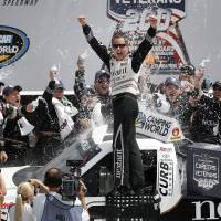 Photo - Driver Johnny Sauter, center, celebrates in Victory Lane after winning the NASCAR Camping World truck series auto race at Michigan International Speedway in Brooklyn, Mich., Saturday, Aug. 16, 2014. (AP Photo/Paul Sancya)