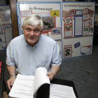 Photo - In this May 14, 2013 photo, Tom Zawistowki, founder of the nonprofit Ohio Liberty Coalition, one of the region's largest groups affiliated with the national tea party movement, poses with a binder of documents he gave to the IRS, in Kent, Ohio. For years, Ohio Liberty Coalition would raise thousands of dollars to bus activists to rallies, run phone banks, rent a tent at a local fair, and knock on roughly 40,000 doors across Ohio to challenge the president and his fellow Democrats in the 2012 elections. All the while, the organization was locked in a battle with the nation's tax enforcement agency over whether it should be granted tax-exempt status. (AP Photo/Tony Dejak)