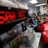 Photo -   Pat Powell, 30, of Atlanta, buys a Powerball lottery ticket at a convenience store, Wednesday, Nov. 28, 2012, in Atlanta.