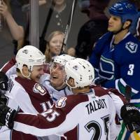 Photo - Colorado Avalanche's Jamie McGinn, Tyson Barrie and Maxime Talbot. from left, celebrate Barrie's goal as Vancouver Canucks' Kevin Bieksa skates past during the third period of an NHL hockey game Thursday, April 10, 2014, in Vancouver, British Columbia. (AP Photo/The Canadian Press, Darryl Dyck)
