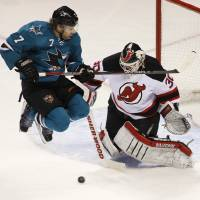 Photo - San Jose Sharks' Brad Stuart, left, jumps up in front of New Jersey Devils goalie Martin Brodeur during the first period of an NHL hockey game on Saturday, Nov. 23, 2013, in San Jose, Calif. (AP Photo/George Nikitin)
