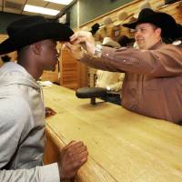 Photo -  Jim Thorpe Award winner Morris Claiborne, left, is fitted for a cowboy hat by Tener's Western Outfitters general manager Heath Jones in Oklahoma City, Monday, February  6, 2012. Tener's gives the recipient of the Jim Thorpe Award a pair of cowboy boots and hat each year. Photo By Steve Gooch, The Oklahoman