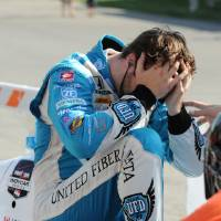 Photo - James Hinchcliffe, of Canada, holds his head after pulling off the course during the inaugural Grand Prix of Indianapolis IndyCar auto race at the Indianapolis Motor Speedway in Indianapolis, Saturday, May 10, 2014. Hinchcliffe was taken from the track on a stretcher and transported to a hospital, where he was diagnosed with a concussion after he was hit in the head with debris. A replay appeared to show debris from a car in front of him flew into his cockpit following a restart. (AP Photo/Greg Huey)