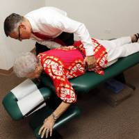Photo - Gregory S. Howard, a chiropractor, works with patient Ruby Walker, 78, at his office in Frederick, Okla. Walker was Howard's first patient when he began his practice in Frederick about 18 years ago.  NATE BILLINGS - NATE BILLINGS
