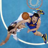 Photo - Golden State Warriors forward David Lee (10) tries to block a shot by New Orleans Hornets center Robin Lopez in the first half of an NBA basketball game in New Orleans, Monday, March 18, 2013. (AP Photo/Gerald Herbert)