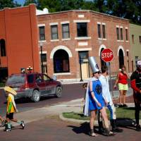 Photo -  A group of superheroes walk the streets of Pauls Valley during International Superhero Day, Saturday, August 4, 2012.