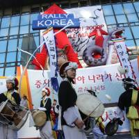 Photo - CORRECTS THE DATE - South Korean dancers in traditional costumes beat their drums during opening ceremony of the Year 2013 trading outside the Seoul Stock Exchange Wednesday, Jan. 2, 2013. The benchmark Korea Composite Stock Price Index (KOSPI) started up 16.69 points, or 0.84 percent, at 2, 013.74. (AP Photo/Ahn Young-joon)