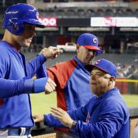 Photo - Chicago Cubs' Anthony Rizzo, left, gets high-fives from manager Rick Renteria, right, and bench coach Brandon Hyde after Rizzo scored a run against the Arizona Diamondbacks in the fourth inning of a spring training baseball game, Friday, March 28, 2014, in Phoenix. (AP Photo/Ross D. Franklin)
