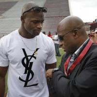 Photo - Adrian Peterson talks with Joe Washington after the University of Oklahoma (OU) football team's annual Red and White Game at Gaylord Family/Oklahoma Memorial Stadium on Saturday, April 14, 2012, in Norman, Okla.  Photo by Steve Sisney, The Oklahoman