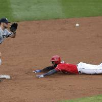 Photo - Texas Rangers' Elvis Andrus (1) steals second as Seattle Mariners second baseman Nick Franklin (6) catches the throw during the second inning of a baseball game, Thursday, April 17, 2014, in Arlington, Texas. (AP Photo/Brandon Wade)