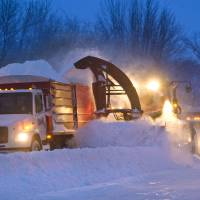 Photo - Snow clearing crews in Pine Island, Minn were out early trying to clear roads before morning commuters headed to work on Thursday, Dec. 20, 2012. The first major snowstorm of the season began its slow eastward march across the Midwest early Thursday, creating treacherous driving conditions and threatening to disrupt some of the nation's busiest airports ahead of the holiday weekend. (AP Photo/The Rochester Post-Bulletin, Jerry Olson)