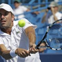 Photo - Julien Benneteau, from France, hits a backhand against Stan Wawrinka, from Switzerland, during a match at the Western & Southern Open tennis tournament, Friday, Aug. 15, 2014, in Mason, Ohio. (AP Photo/Al Behrman)