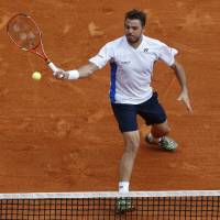 Photo - Stanislas Wawrinka of Switzerland, returns the ball to Roger Federer of Switzerland during the final match of the Monte Carlo Tennis Masters tournament in Monaco, Sunday, April 20, 2014. (AP Photo/Michel Euler)