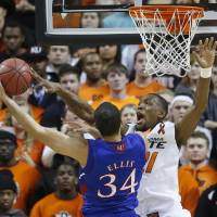 Photo - Oklahoma State forward Kamari Murphy (21) blocks a shot by Kansas forward Perry Ellis (34) during the first half of an NCAA college basketball game in Stillwater, Okla., Wednesday, Feb. 20, 2013. (AP Photo/Sue Ogrocki)