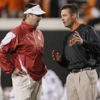 Photo - OU head coach Bob Stoops, left, and OSU head coach Mike Gundy talk before the Bedlam college football game between the University of Oklahoma Sooners (OU) and the Oklahoma State University Cowboys (OSU) at Boone Pickens Stadium in Stillwater, Okla., Saturday, Nov. 27, 2010. Photo by Nate Billings, The Oklahoman ORG XMIT: KOD
