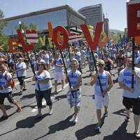"""Photo - In this June 8, 2014, photo, American Express workers carry giant, cutout letters that spelled, """"Love=Love,"""" the theme of the of the gay pride parade, in Salt Lake City. Corporations have increased visibility this summer at gay pride parades around the country as same-sex marriage bans fall in the courts and polls show greater public acceptance of gay marriage. (AP Photo/Rick Bowmer)"""