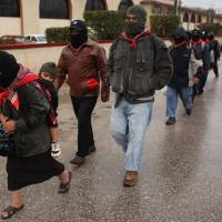Photo - Masked Mayan Indians who are members of the Zapatista National Liberation Army (EZLN) march in line to the mayor's office in San Cristobal de las Casas, Chiapas state, Mexico, Friday, Dec. 21, 2012. On Friday, Zapatistas in several cities are marching to the city mayor's office for a gathering where they will listen to a message from their leaders. (AP Photo/Ivan Castaneira)