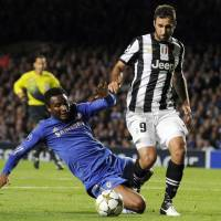 Photo -   Juventus' Mirko Vucinic, right, is tackled by Chelsea's John Obi Mikel during their Champions League group E soccer match at Stamford Bridge, London, Wednesday, Sept. 19, 2012. (AP Photo/Tom Hevezi)