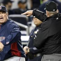 Photo - First base umpire Bob Davidson tosses out Boston Red Sox manager John Farrell who objected to MLB's ruling of a an overturned fourth-inning force out at first base in a baseball game against the New York Yankees at Yankee Stadium in New York, Sunday, April 13, 2014.  The Yankees Brian McCann scored on the play. (AP Photo/Kathy Willens)