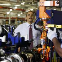 Photo - President Barack Obama watches a worker during a visit to the heavy duty engines line at the Daimler Detroit Diesel plant in Redford, Mich., Monday, Dec. 10, 2012. (AP Photo/Charles Dharapak)
