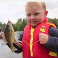 Photo -       In a video from May 29, 2011, 3-year-old Teddy unknowingly catches a small fish while out on the lake with his dad. (YouTube screenshot)