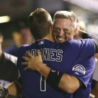 Photo - Colorado Rockies' Brandon Barnes, front, hugs teammate Michael Cuddyer after he scored on a single hit by pinch-hitter Drew Stubbs against the Cincinnati Reds in the eighth inning of the Rockies' 10-5 victory in a baseball game in Denver on Sunday, Aug. 17, 2014. The game is being made up after it was postponed on Saturday by a water main break that left the stadium waterless. (AP Photo/David Zalubowski)