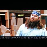 Photo - Fans were able to watch tonight's episode of Duck Dynasty on Big Hoss, one of the stars, Willie Robertson on screen here, and his wife were in attendance at TMS. Texas Motor Speedway debuted their new Big Hoss TV screen, a 218 x 94 foot screen over the east grandstands of the racetrack, Wednesday, March 19, 2014. The first show to be seen on the screen by the public is Wednesday's episode of