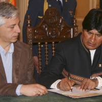 Photo - In this photo released by Bolivia's Presidency Press Office, Bolivia's President Evo Morales signs a decree allowing the takeover of shares in Empresa de Electricidad de La Paz (Electropaz) and Empresa de Luz y Fuerza de Oruro (Elfeo), Vice President Alvaro Garcia Linera at the government palace in La Paz, Bolivia, Saturday, Dec. 29, 2012. The decree read by Morales also calls for Iberdrola to receive indemnification after an independent firm is hired within 180 days to determine the value of the nationalized shares. Bolivia's Vice President Alvaro Garcia Linera is pictured at left. (AP Photo/Presidency Press Office, Jose Lirauze)