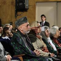 Photo - Afghan President Hamid Karzai sits among the audience prior to his nationally televised speech about the state of Afghan women in Kabul, Afghanistan, Sunday, March, 10, 2013. Karzai on Sunday accused the Taliban and the U.S. of working in concert to convince Afghans that violence will worsen if most foreign troops leave as planned by the end of next year. Karzai says two deadly suicide bombings on Saturday show the insurgent group is conducting attacks to help show that international forces will still be needed to keep the peace after their current combat mission ends in 2014. (AP Photo/Ahmad Jamshid)