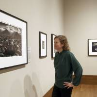 Photo - This March 14, 2014 photo shows Karen Hellman, Assistant Curator Department of Photographs examining a photo exhibit entitled,