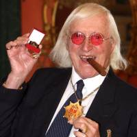 Photo -   FILE - This March 25, 2008 file photo shows Jimmy Savile holding a medal in London. At Savile's funeral in 2011, the priest delivering the homily was emphatic: the DJ and television host