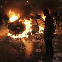 Photo - A masked protester watches a vehicle burn during clashes between opponents of Egyptian President Mohammed Morsi and his Islamist supporters in Alexandria, Egypt, Friday, Dec. 21, 2012. Thousands of Islamists clashed with their opponents on Friday in Egypt's second largest city, Alexandria as the two sides hurled stones and youth protesters sat fire on vehicles belonging to Islamists, a day before the second leg of voting on a proposed constitution that has deeply polarized the nation.(AP Photo)