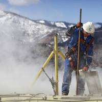 Photo - In this March 29, 2013 photo, a worker checks a dipstick to check water levels and temperatures in a series of tanks at an Encana Oil & Gas (USA) Inc. hydraulic fracturing operation at a gas drilling site outside Rifle, Colorado. In the 2000s, large investors in so-called clean technology wanted to finance companies that would help eliminate the world's dependence on oil, natural gas and coal. But in 2013, clean technology investment funds are not trying to replace the fossil fuel industry, they're trying to help it by financing companies that can make mining and drilling less dirty. (AP Photo/Brennan Linsley)