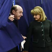 Photo - Romania's President Traian Basescu, left, exits a voting cabin as his wife Maria, right, stands by, in Bucharest, Romania, Sunday, Dec. 9, 2012. Millions of Romanians braved rain and snow Sunday as they went to the polls for a parliamentary election that center-left government is expected to win a, but the result could lead to more of the political instability that has plagued the impoverished Balkan nation this year. (AP Photo)